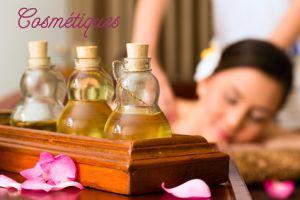 3 bouteilles d'huiles essentielles en premier plan, avec une femme se faisant masser en second plan.
